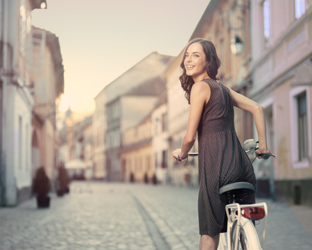 toothy smile: beautiful young woman with bicycle stops to turn heads and give us a toothy smile to camera in a European city at sunset