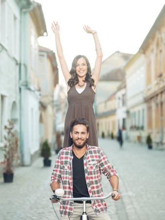 jovenes felices: joven pareja en las vacaciones que se divierte en una bicicleta de alquiler en la ciudad, en las mujeres de verano con las manos arriba