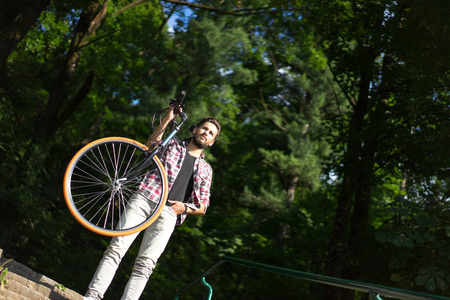 powerful man: a powerful man hanging his bike on his shoulder, staying on stairs, glancing far away.