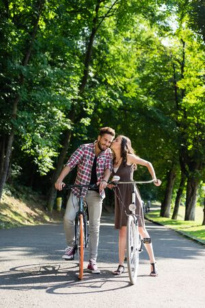 be kissed: handsome young man with blue eyes stops cycling to be kissed on the cheek of a beautiful young woman