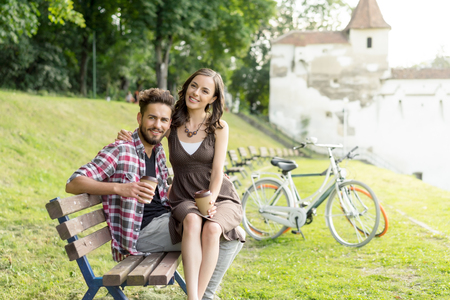sandal tree: a sweet couple having a coffee, the girl staying comfortably in his lap and both are smiling Stock Photo