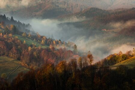 haycock: the hill is covered by the rusty colours of autumn, fog and spread house and chalet
