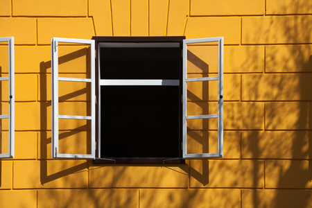house windows: open window with white frames, yellow bricks and some shadows
