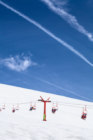 piste: skiers taking a rest and going up on the peak of a ski piste with red ski lifts in Romanians mountains