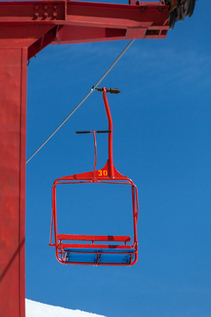 no pase: empty chair of ski lift going down from the peak of the mountain