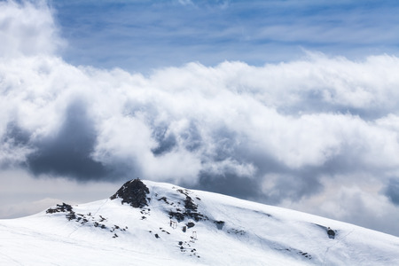 cloud drift: dark clouds and few frosty snow on winter in a ski resort Stock Photo