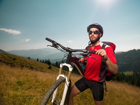 mountain biker: mountain biker on a meadow, along bike, looking forward, pushing bike