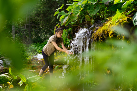 mountain peek: woman in nature, with green leaves, washing her hands at the waterfall Stock Photo
