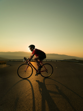 road bike: cyclist on road bike in motion at sunset Stock Photo