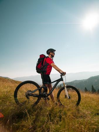 red mountain: mountain biker on a meadow, along bike, looking forward