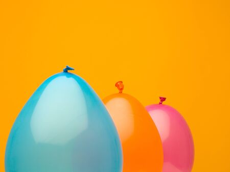 clean landscape composition made from three balloons aquamarine, yellow, and orange against a dark orange background Stock Photo