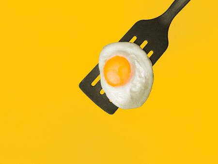 sunny side up: Sunny side up egg on a spatula 34-overhead view on yellow background