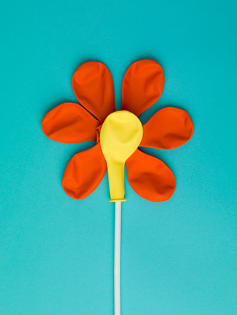 colourful flower pattern made from delated orange and yellow balloons on a sky blue background Stock Photo