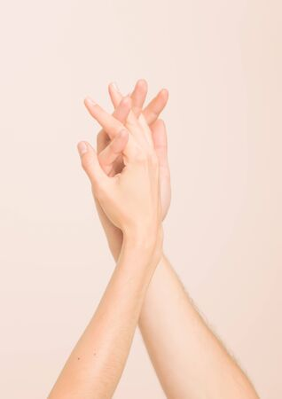 tenderly: Hands of man and woman tenderly touching each other on clean skin tone background