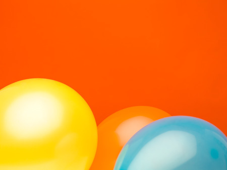 three-dimensional balloons yellow, orange and blue against red background