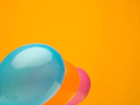 blow up: clean landscape composition made from three balloons aquamarine, yellow, and orange against a dark orange background Stock Photo