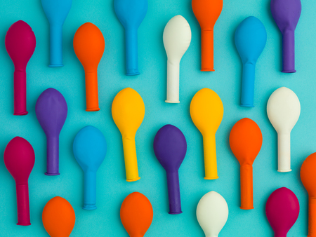 deflated: arranged pattern of colourful deflated balloons on a blue background Stock Photo