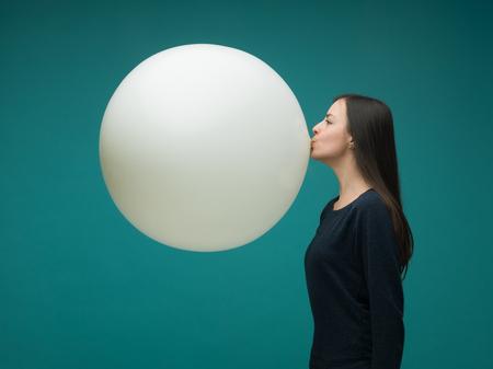 grappig jonge vrouw met lang donker haar opblazen van enorme ballon op een blauwe achtergrond