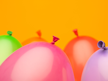 composition made of five upright balloons with tails on a yellow background