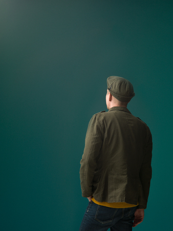 unknown men: fashionable military style dressed person rear view looking at a dark aquamarine background Stock Photo