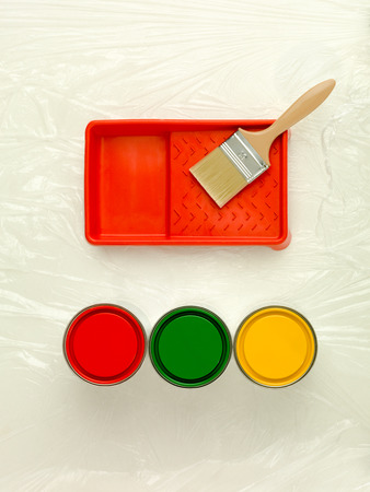 paintjob: clean upper-view of three paint cans red green and yellow paint-tray and paintbrush Stock Photo