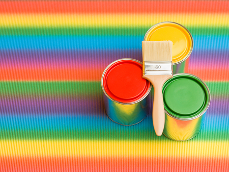 three paint cans yellow green and red on rainbow background Stock Photo