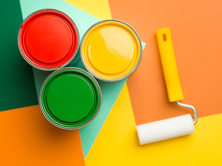 three cans  yellow green and red and paint roll on colourful geometrical background
