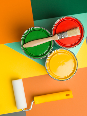 three cans  yellow green and red and paint brush and roll on colourful geometrical background Stock Photo