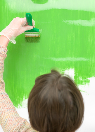 wall paintings: Rear view shot of a casual woman painting the wall in the living room. Stock Photo