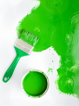 Landscape image green paint brush with green splash and can. top view with copy space