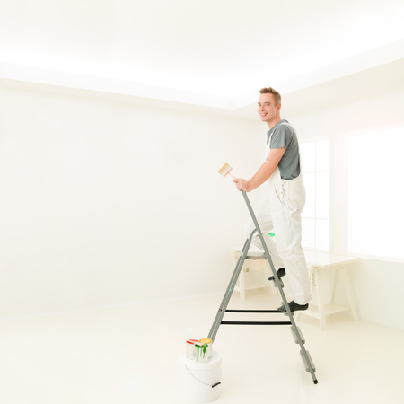 Square portrait young man laughing standing on a ladder with a  paint brush, bright white  home. repair, building, renovation and people concept Stock Photo