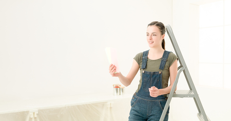 banner image of chic young woman choosing the colour foe the walls in her new luminous home
