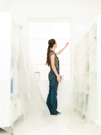 refurbishing: full length image of woman painting her bright white home in front of a window Stock Photo