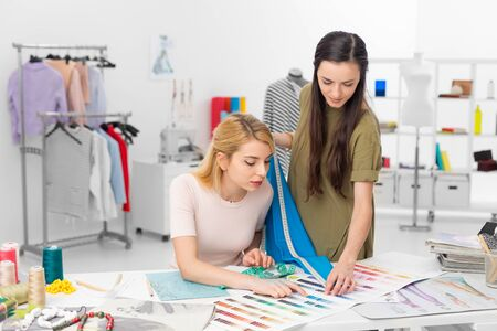 fashion designer and client choosig color for new dress in the workshop Stock Photo
