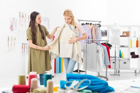 Customer tries new clothing collection of a successful fashion designer in her showroom Stock Photo
