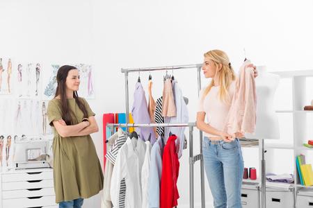 mujer elegante: El cliente intenta nueva colección de ropa de un diseñador de moda exitoso en su showroom