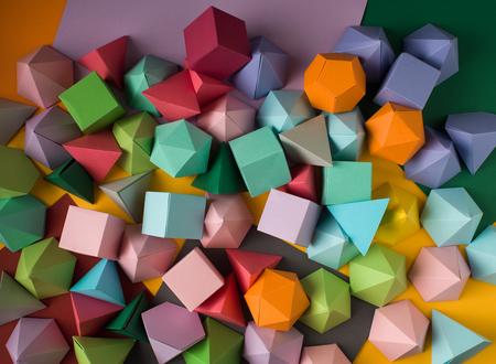 solid figure: Sfondo geometrico astratto colorato con figure solide tridimensionali. Piramide Dodecahedron cubo rettangolare prisma disposto su carta colorata.