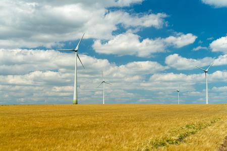 Eolian generators in a beautiful wheat field. eolian turbine farm,wind turbine, wind field with wind turbines. Wind propeller. Wheat Fiel Agriculture. Stock Photo