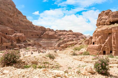 PETRA, JORDAN - APRIL 25, 2016: Tourists visit the Petra's ancient amphitheater.Temples, tombs, theatres and other buildings are scattered over 400 square miles. 新聞圖片