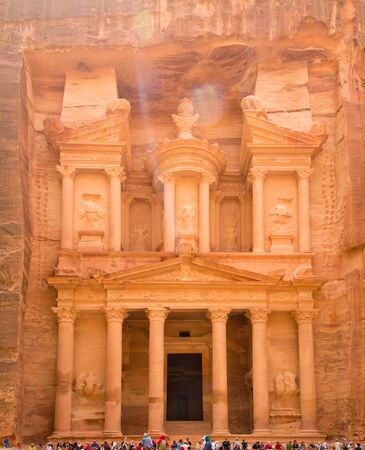 PETRA, JORDAN, April 25, 2016: Visitors sit on a ledge of the amazing Treasury, carved from stone in the rose red city of Petra, a UNESCO World Heritage Site.