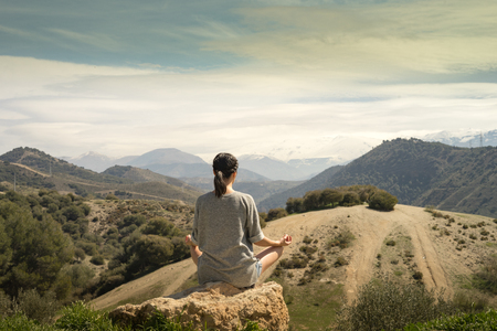 Young woman meditating in front of Sierra Nevada Mountain