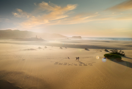 couple with their hand up in the air on beautiful white sand beach, dreamers writen down on the sand- bird eye view