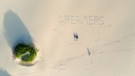 couple laying on beautiful white sand beach, dreamers writen down on the sand- bird eye view