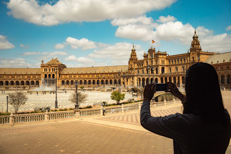 Sevilla Plaza de Espana bridge Andalusia Spain Girl making photo of famous historic touristic place at her travel. Backpack travel concept.