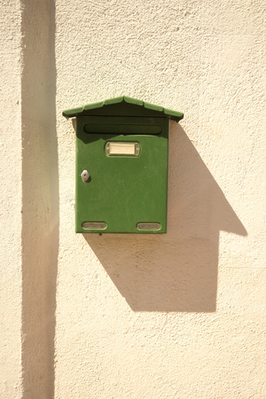 Green mailbox in the sun on a house's wall with shadow