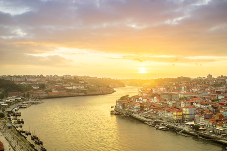 Porto, Portugal old town ribeira aerial promenade view with colorful houses, Douro river and boats at sunset
