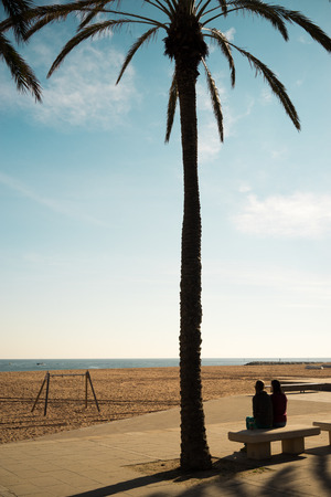 silhouette of two women sitting on a beach back