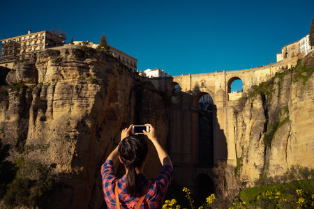 Woman traveler taking photo of the old city and of Ronda, one of the most famous white villages of Malaga, Andalusia, Spain