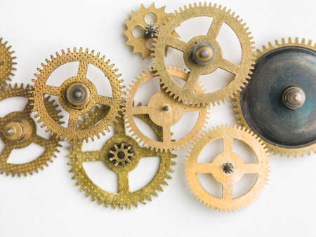 Metal collage of clockwork gears on white background