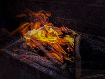 closeup of flames and burning woods in a fireplace
